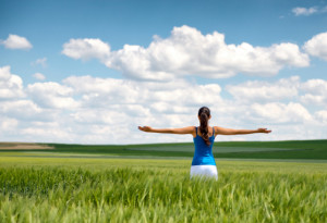 Image of a girl in a wheat field standing in the distance with her back to the camera and her arms o